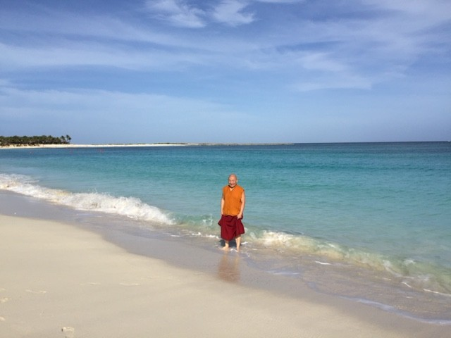 Lama Migmar touching the water in Bahamas.